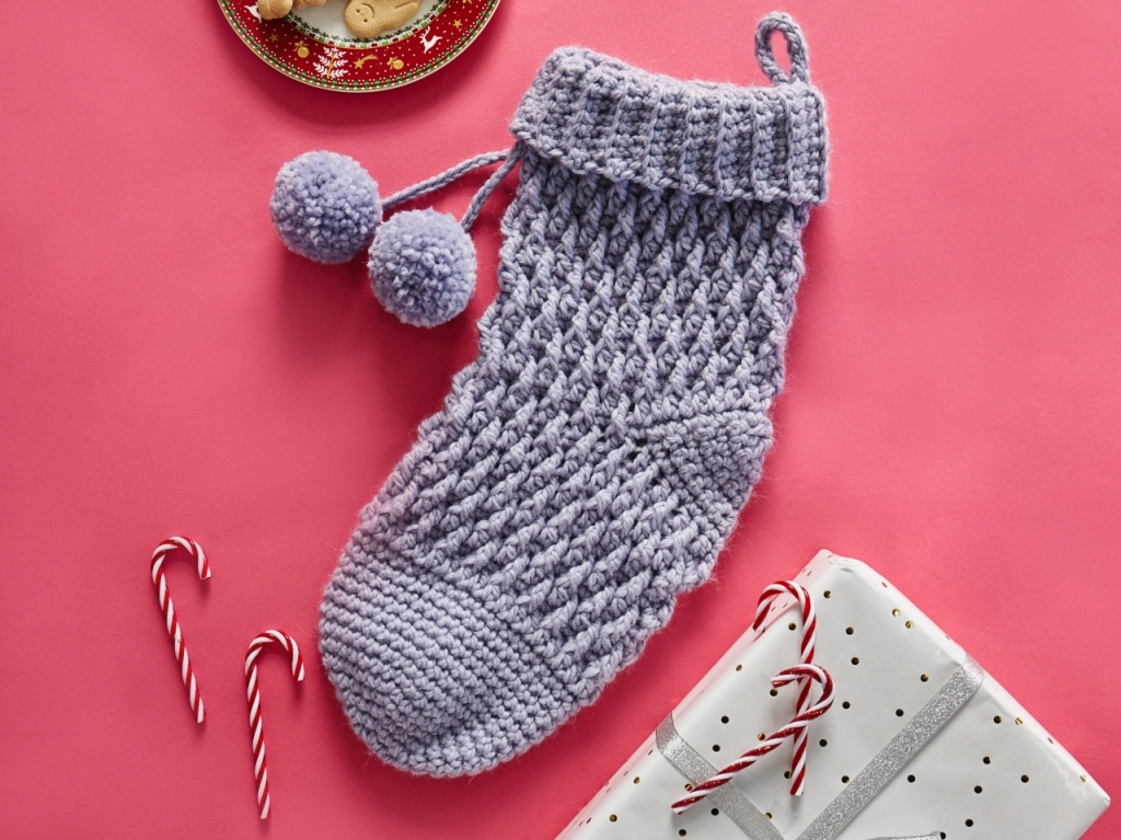 Chunky crocheted textured lilac Christmas stocking on a pink background