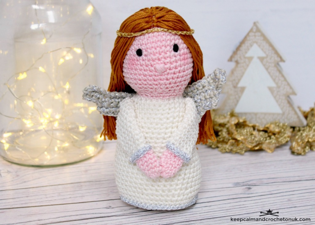 Crochet angel next to some twinkly lights in a Christmas scene